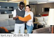 Купить «Couple inspecting furniture prices in store», фото № 30696478, снято 19 февраля 2018 г. (c) Яков Филимонов / Фотобанк Лори