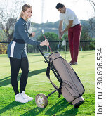 Купить «Woman golfer deciding on right club while her male partner hitting ball», фото № 30696534, снято 20 сентября 2019 г. (c) Яков Филимонов / Фотобанк Лори