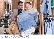 Купить «Smiling woman and man are choosing clothes and looking on jeans blouse», фото № 30696570, снято 12 марта 2018 г. (c) Яков Филимонов / Фотобанк Лори