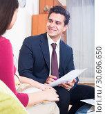 Купить «Insurance agent and customer discussing agreement terms in living room», фото № 30696650, снято 26 мая 2019 г. (c) Яков Филимонов / Фотобанк Лори
