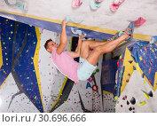 Купить «Male practicing on artificial boulder without safety belts», фото № 30696666, снято 9 июля 2018 г. (c) Яков Филимонов / Фотобанк Лори