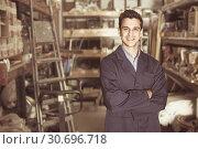 Купить «Portrait of young man in uniform in building shop», фото № 30696718, снято 26 июля 2017 г. (c) Яков Филимонов / Фотобанк Лори