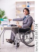 Купить «Young handsome employee in wheelchair at the office», фото № 30697134, снято 23 ноября 2018 г. (c) Elnur / Фотобанк Лори