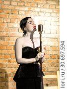 Beautiful young woman singing on a vintage microphone on brick wall background. Стоковое фото, фотограф Евгений Ткачёв / Фотобанк Лори