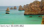 Купить «People on canoe near Dona Ana beach (Praia Dona Ana) and limestone rocky sea coast, Portugal», видеоролик № 30699482, снято 21 марта 2019 г. (c) Serg Zastavkin / Фотобанк Лори