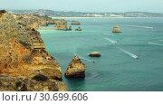Купить «Limestone rocky sea coast near Lagos, Algarve region, Portugal», видеоролик № 30699606, снято 23 марта 2019 г. (c) Serg Zastavkin / Фотобанк Лори