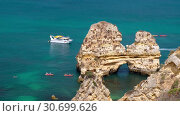 Купить «People on canoe near Camilo beach and limestone rocky sea coast, Portugal», видеоролик № 30699626, снято 23 марта 2019 г. (c) Serg Zastavkin / Фотобанк Лори