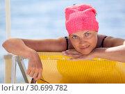 Купить «Довольная загорелая женщина лежит в шезлонге на пляже с очками в руке и смотрит в камеру», фото № 30699782, снято 23 июля 2018 г. (c) Кекяляйнен Андрей / Фотобанк Лори