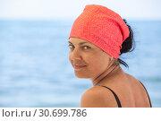 Купить «Портрет красивой загорелой женщины с красной косынкой на голове, море на заднем плане», фото № 30699786, снято 23 июля 2018 г. (c) Кекяляйнен Андрей / Фотобанк Лори
