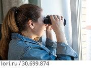 Купить «Любопытная женщина смотрит в окно с биноклем из комнаты», фото № 30699874, снято 16 апреля 2019 г. (c) Кекяляйнен Андрей / Фотобанк Лори
