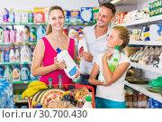 Купить «Smiling young family with girl choosing detergent», фото № 30700430, снято 11 июля 2017 г. (c) Яков Филимонов / Фотобанк Лори