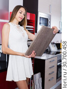 Купить «Girl choosing kitchen fronts materials», фото № 30700458, снято 15 июня 2017 г. (c) Яков Филимонов / Фотобанк Лори