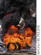 Купить «Сильный пожар, горящие автомобильные покрышки, черный ядовитый дым в небе», фото № 30703510, снято 18 апреля 2019 г. (c) А. А. Пирагис / Фотобанк Лори