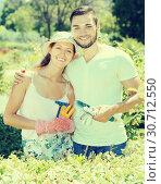Купить «Cheerful couple in flowers garden smiling», фото № 30712550, снято 27 июня 2019 г. (c) Яков Филимонов / Фотобанк Лори