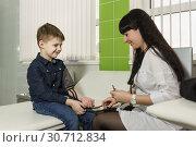 Купить «Медработник измеряет мальчику артериальное давление. Ребенок смотрит с улыбкой», фото № 30712834, снято 17 марта 2019 г. (c) Наталья Гармашева / Фотобанк Лори