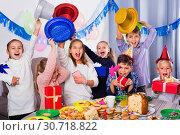Купить «Boys and girls handing gifts to each other during dinner», фото № 30718822, снято 26 июня 2019 г. (c) Яков Филимонов / Фотобанк Лори