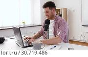 Купить «happy young man with laptop and microphone at home», видеоролик № 30719486, снято 2 мая 2019 г. (c) Syda Productions / Фотобанк Лори