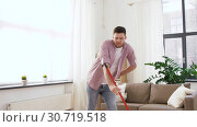 Купить «man with broom cleaning and having fun at home», видеоролик № 30719518, снято 2 мая 2019 г. (c) Syda Productions / Фотобанк Лори