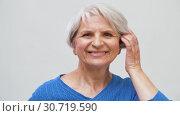 Купить «portrait of smiling senior woman touching her hair», видеоролик № 30719590, снято 6 мая 2019 г. (c) Syda Productions / Фотобанк Лори