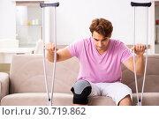 Купить «Young man with injured knee recovering at home», фото № 30719862, снято 4 сентября 2018 г. (c) Elnur / Фотобанк Лори