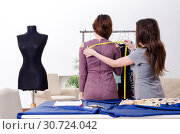Купить «Young beautiful female tailor taking measurements», фото № 30724042, снято 7 февраля 2019 г. (c) Elnur / Фотобанк Лори