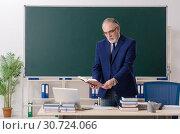Купить «Aged male teacher in front of chalkboard», фото № 30724066, снято 20 декабря 2018 г. (c) Elnur / Фотобанк Лори