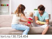 Купить «Young family helping each other after injury», фото № 30724454, снято 21 сентября 2018 г. (c) Elnur / Фотобанк Лори