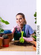 Купить «Young female gardener with plants indoors», фото № 30724998, снято 26 ноября 2018 г. (c) Elnur / Фотобанк Лори
