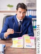 Купить «Young handsome employee planning his work activity», фото № 30725514, снято 1 августа 2018 г. (c) Elnur / Фотобанк Лори