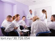 Купить «Young students of medical faculty conversation with teacher», фото № 30726054, снято 5 октября 2017 г. (c) Яков Филимонов / Фотобанк Лори