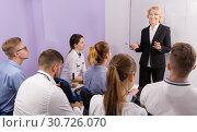 Купить «Female teacher lecturing to students at auditorium», фото № 30726070, снято 5 октября 2017 г. (c) Яков Филимонов / Фотобанк Лори