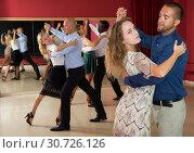 Купить «Positive adult couples dancing tango together in modern studio», фото № 30726126, снято 4 октября 2018 г. (c) Яков Филимонов / Фотобанк Лори