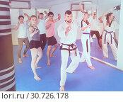 Купить «Young adult trainees practicing in karate class», фото № 30726178, снято 8 апреля 2017 г. (c) Яков Филимонов / Фотобанк Лори