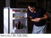 Купить «Man breaking diet at night near fridge», фото № 30726582, снято 8 февраля 2019 г. (c) Elnur / Фотобанк Лори
