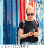 Купить «Woman using smartphone against colorful graffiti wall in New York city, USA.», фото № 30731618, снято 4 апреля 2020 г. (c) Matej Kastelic / Фотобанк Лори