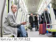 Купить «Beautiful blonde woman using smart phone while traveling by metro public transport.», фото № 30731622, снято 13 января 2019 г. (c) Matej Kastelic / Фотобанк Лори