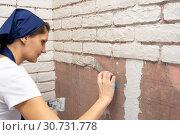 Девушка штукатур делает дизайнерскую авторскую имитацию кирпичной кладки на стене квартиры. Стоковое фото, фотограф Иванов Алексей / Фотобанк Лори