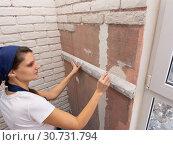 Штукатур наносит горизонтальную линию карандашом на стене используя алюминиевое правило. Стоковое фото, фотограф Иванов Алексей / Фотобанк Лори