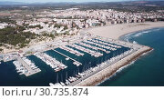 Купить «Picturesque aerial view of Mediterranean coastal town of Torredembarra with yachts moored in harbor, Tarragona, Spain», видеоролик № 30735874, снято 18 марта 2019 г. (c) Яков Филимонов / Фотобанк Лори