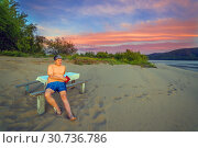 Купить «A man sits on a bench on a wild sandy beach on the Volga. After sunset», фото № 30736786, снято 17 августа 2018 г. (c) Акиньшин Владимир / Фотобанк Лори