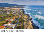 Купить «Aerial view of small town with red roofs on coastline Atlantic ocean. Top View of Azenhas Do Mar, Sintra, Portugal», фото № 30736986, снято 21 апреля 2019 г. (c) Кирилл Трифонов / Фотобанк Лори