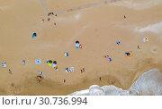Купить «Aerial view of a sandy beach line full of bathers and colorful umbrellas», фото № 30736994, снято 29 апреля 2019 г. (c) Кирилл Трифонов / Фотобанк Лори