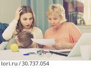 Купить «Two women are puzzled of problems with filling utility bills with laptop», фото № 30737054, снято 15 февраля 2018 г. (c) Яков Филимонов / Фотобанк Лори