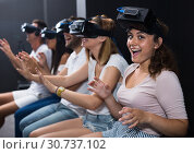 Young female is watching exciting movie with friends in VR glasses. Стоковое фото, фотограф Яков Филимонов / Фотобанк Лори