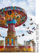 Купить «People ride the chain carousel in an amusement park. Cheboksary, Russia, 05/11/2019», фото № 30737554, снято 11 мая 2019 г. (c) Александр Якимов / Фотобанк Лори