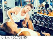 Купить «Young positive man making biceps curls in gym», фото № 30738854, снято 4 октября 2016 г. (c) Яков Филимонов / Фотобанк Лори
