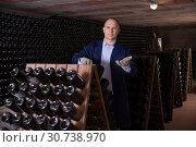 Купить «Male inspecting wine bottles in wine cellar», фото № 30738970, снято 22 января 2018 г. (c) Яков Филимонов / Фотобанк Лори