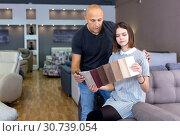Купить «Husband and wife in process of choosing upholstery fabric», фото № 30739054, снято 29 октября 2018 г. (c) Яков Филимонов / Фотобанк Лори