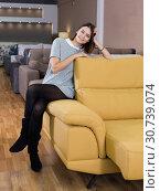 Купить «Woman testing sofa in furniture store», фото № 30739074, снято 29 октября 2018 г. (c) Яков Филимонов / Фотобанк Лори