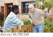 Купить «Disgruntled men talking in backyard», фото № 30739134, снято 15 декабря 2018 г. (c) Яков Филимонов / Фотобанк Лори